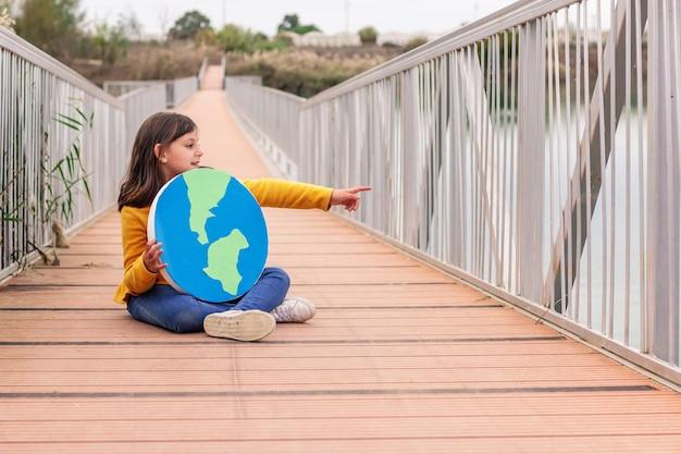 Menina olhando para o horizonte e apontando com a mão, o mundo em suas mãos em uma ponte assentada, conceito de mudança climática