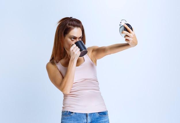 Menina olhando para o relógio enquanto bebe uma xícara de café.