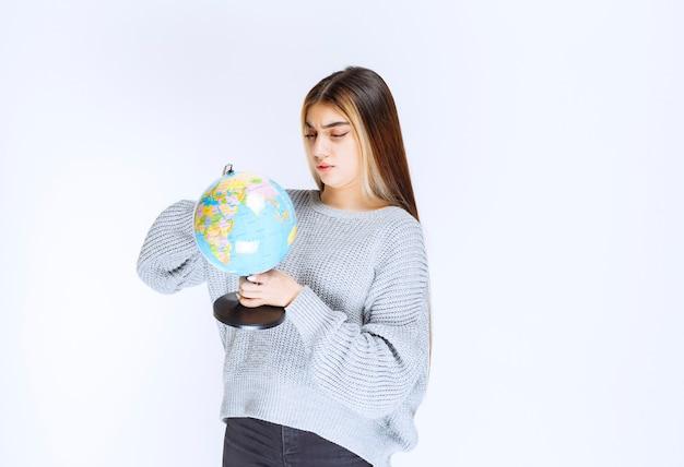 Menina olhando para um globo do mundo e tentando encontrar locais sobre ele.