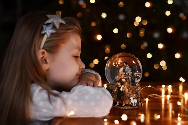 Menina olhando para uma bola de vidro com uma cena do nascimento de jesus cristo perto da árvore de natal
