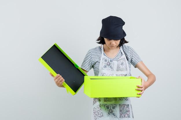 Menina olhando para uma caixa de presente com vestido de cozinha e parecendo focada,