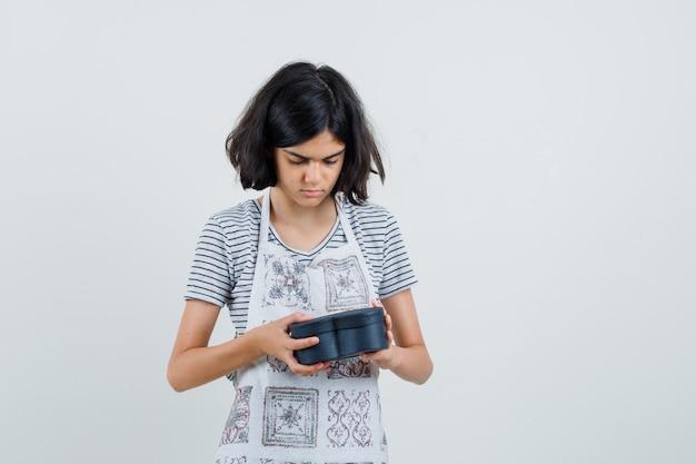 Menina olhando para uma caixa de presente de camiseta, avental e curiosa,