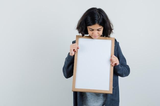 Menina olhando para uma moldura vazia em camiseta, jaqueta