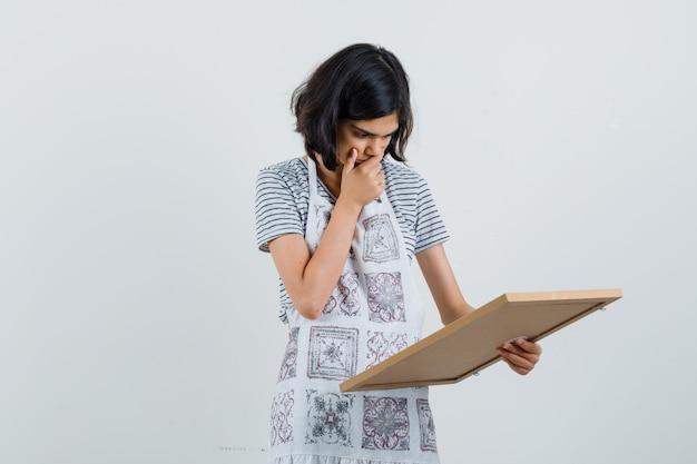 Menina olhando para uma moldura vazia em uma camiseta, avental e parecendo surpresa,