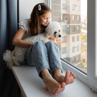 Menina olhando pela janela com o cachorro em casa