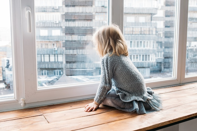 Menina olhando pela janela em casa