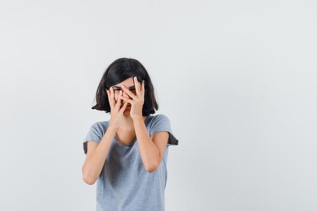 Menina olhando por entre os dedos em t-shirt e parecendo curiosa. vista frontal.