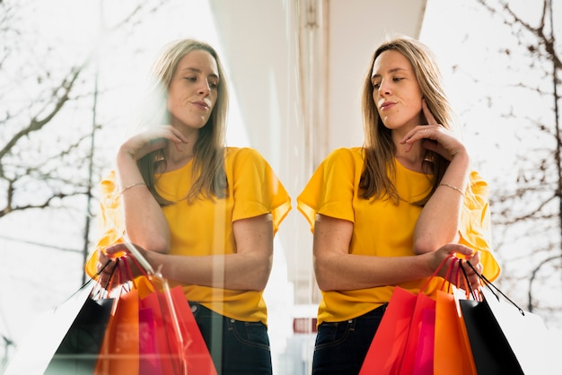 Menina olhando seu reflexo, segurando sacolas de compras