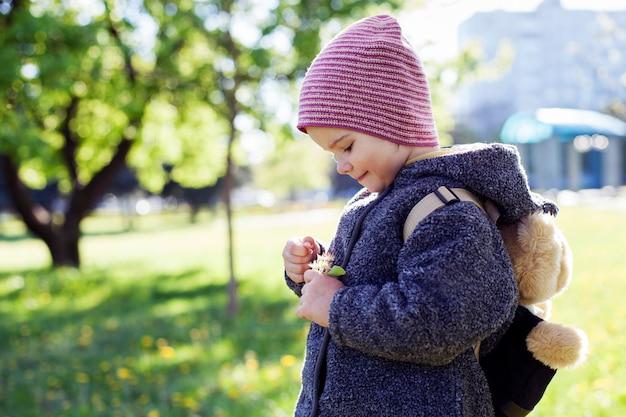 Menina olhando uma flor nas mãos