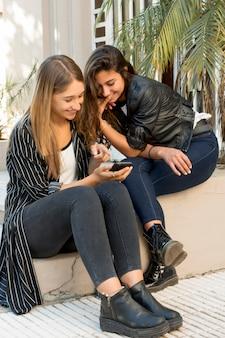 Menina, olhar, dela, amigo, mostrando, algo, ligado, telefone móvel, em, ao ar livre