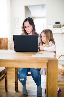 Menina, olhar, dela, mãe, usando computador portátil, ligado, tabela madeira