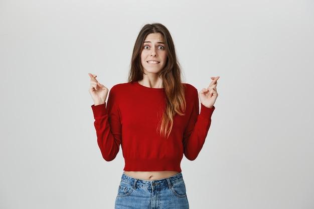 Menina oprimida esperançosa implorando, cruze os dedos boa sorte, mordendo o lábio nervoso