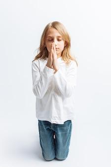 Menina orando de joelhos a deus, comunhão com deus, doce e bonita