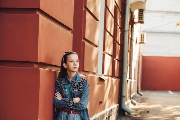 Menina orgulhosa em roupas jeans fica perto de um antigo prédio bonito restaurado.