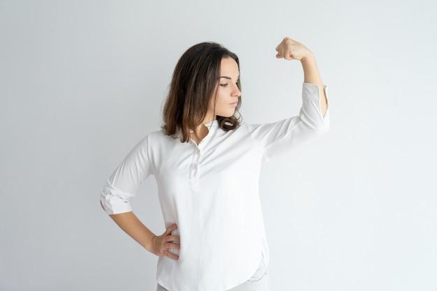 Menina orgulhosa séria que mostra o gesto da força.