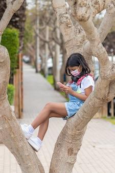 Menina ouvindo música com fones de ouvido em uma árvore