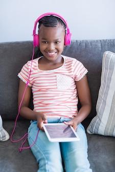 Menina ouvindo música do tablet digital