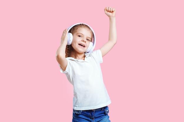 Menina ouvindo música em fones de ouvido. filho bonito, desfrutando de música de dança feliz, fechar os olhos e sorrir posando