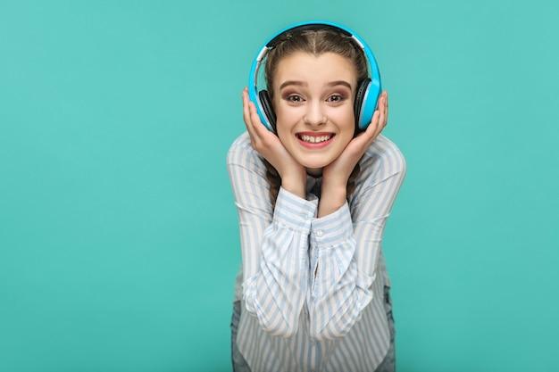 Menina ouvindo música, segurando seus fones de ouvido e olhando para a câmera com um sorriso cheio de dentes