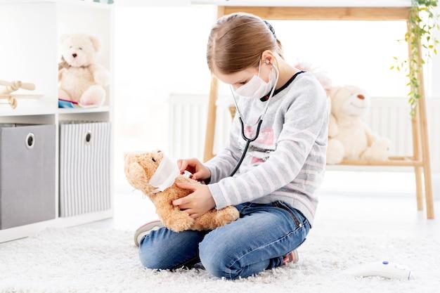 Menina ouvindo pelo estetoscópio ursinho de pelúcia, conceito médico