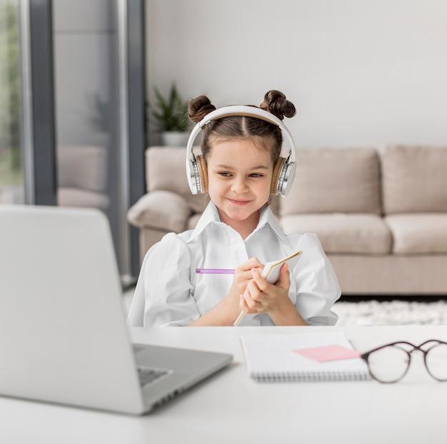 Menina ouvindo seu professor através de fones de ouvido dentro de casa