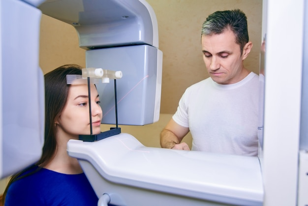 Menina-paciente fica em um tomógrafo, um médico perto do painel de controle
