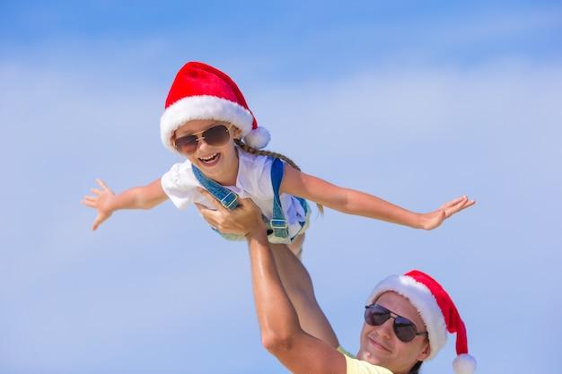 Menina, pai feliz no chapéu de papai noel durante as férias de praia