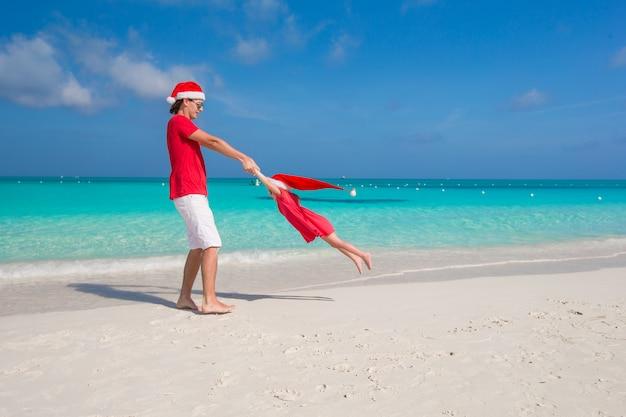 Menina, pai feliz no chapéu de papai noel se divertindo durante as férias de verão
