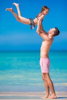 Menina, pai feliz se divertindo durante as férias de praia