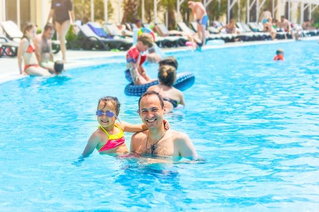 Menina, pai feliz se divertindo juntos na piscina ao ar livre