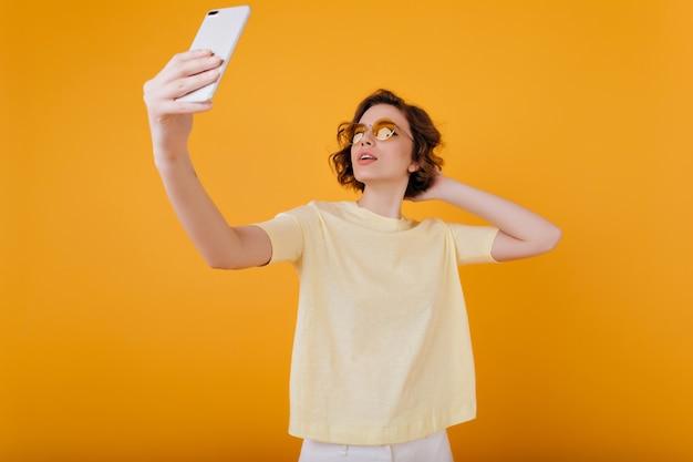 Menina pálida com tatuagem no braço tirando foto de si mesma em um quarto amarelo