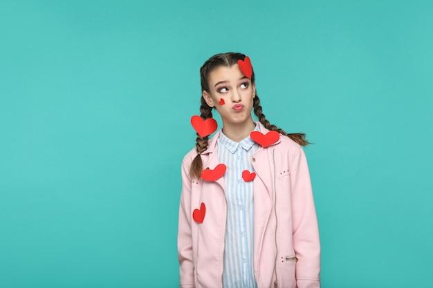 Menina parada com vários adesivos vermelhos colados e olhando para longe com uma cara confusa