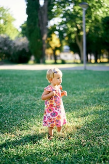 Menina parada de lado em um gramado verde no parque