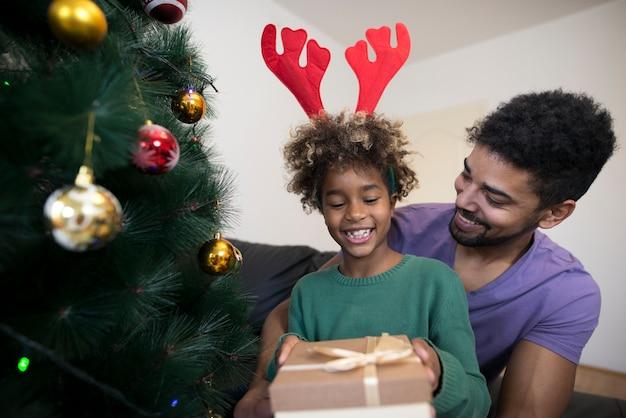Menina parada perto da árvore de natal desembrulhando a caixa de presente parecendo surpresa