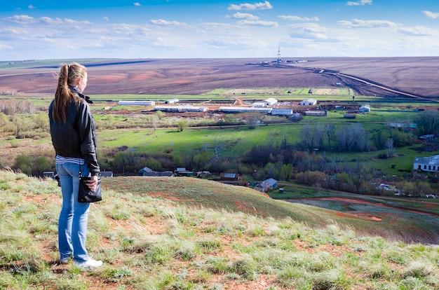 Menina parece de uma colina em uma paisagem rural com sondas de perfuração no campo