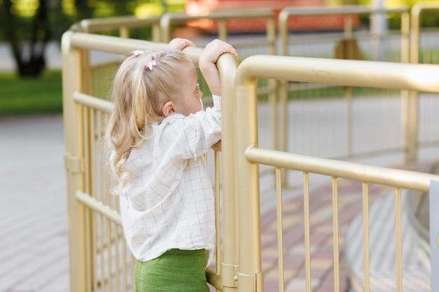 Menina parece longe no parque de verão