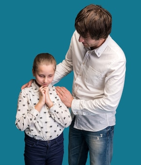 Menina parecendo triste com o pai em uma parede azul