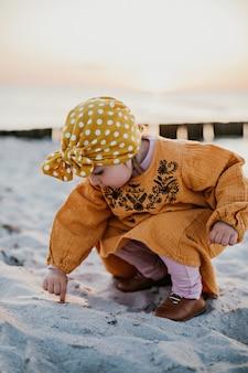 Menina passando o dedo na areia da praia durante o pôr do sol