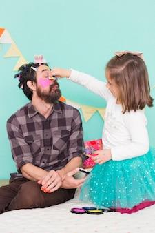 Menina passando o tempo com o pai fazendo maquiagem