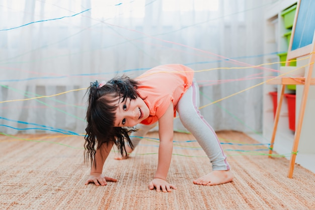 Menina passando por uma teia de corda
