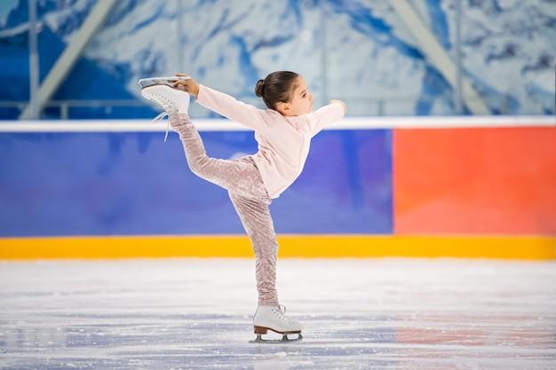 Menina patinadora em um agasalho de treino rosa claro com um sorriso