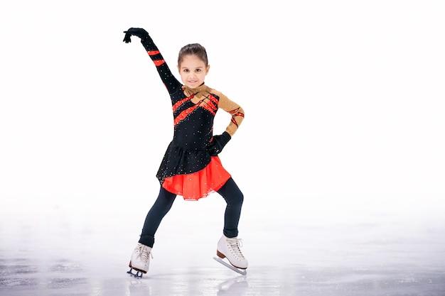 Menina patinadora em um lindo vestido preto e vermelho patinando em uma arena de gelo coberta