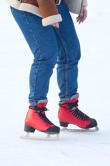 Menina patinando em uma pista de gelo. hobbies e esportes. férias e atividades de inverno