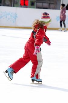 Menina patinando na pista de gelo
