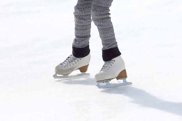 Menina patins na pista de gelo. esporte e entretenimento. descanso e férias de inverno.