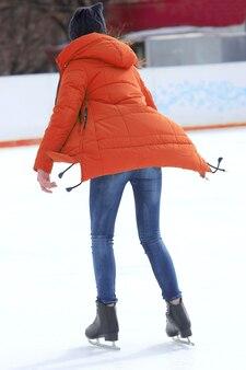 Menina patins na pista de gelo. esportes, hobbies e recreação de pessoas ativas