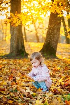 Menina pegando folhas de plátano