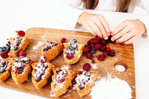 Menina pegando frutas frescas para bolos