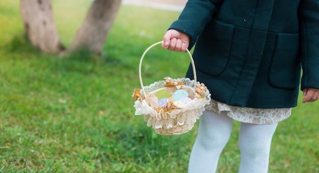 Menina pegando um detalhe de cesta de páscoa em um fundo de jardim