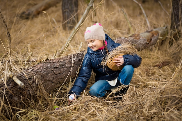Menina pegando um ovo de páscoa debaixo de um tronco na floresta